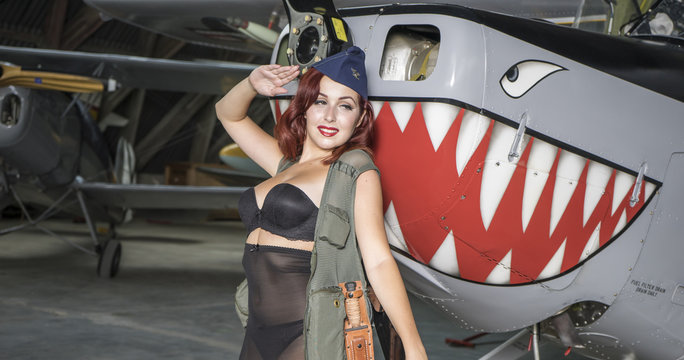 Vintage, redhead woman dressed as a soldier next to a plane of the second world war, American pinup in the style of the 40s. sensual and sexy woman