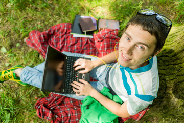 Photo from above of man with laptop on red plaid
