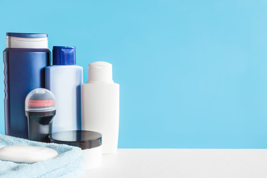 Different, colorful beauty toiletries, cream jar, soap and towels on the blue background. Body relax and care products for men. Empty place for text or a logo. Front view.