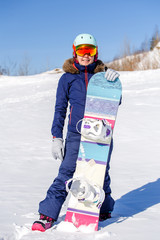 Full-length photo of athlete in helmet with snowboard in winter day