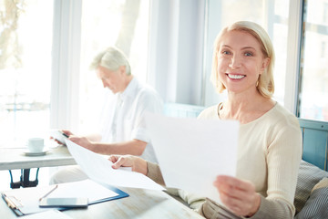 Happy mature businesswoman working with papers on background of colleague