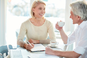 Friendly mature businesswoman looking at he rcolleague during their conversation at meeting in cafe