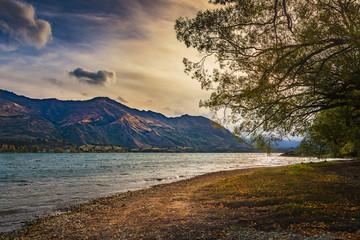Sunset on lakeside of Wanaka, New Zealand with mountain, golden sky and lake.