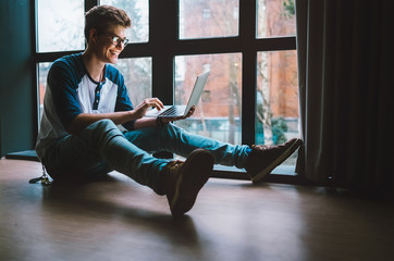 Guy with laptop sits on the floor at home
