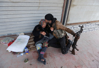 A Turkish-backed Free Syrian Army fighter kisses an old woman in Afrin