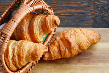 Corissants in the basket on wooden background