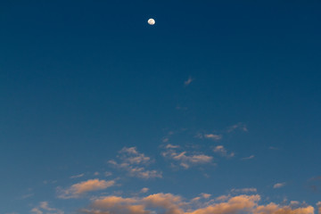 Moon on blue sky high over pink clouds at sunset