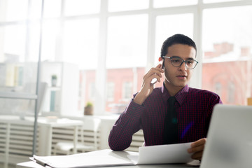 Businessman working with papers and laptop and discussing work on the phone