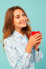 Young woman holding a cup of tea or coffee over blue background