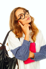 Pretty thoughtful student with book wearing glasses over white background