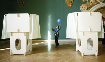 A child plays with a balloon near voting booths inside a building of the Kazansky railway terminal during the presidential election in Moscow