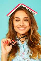 Pretty smiley student with book over her head wearing glasses over blue background