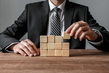 Businessman building a structure with wooden cubes on table.Success and business strategy concept.