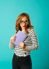 Pretty student with book wearing glasses over blue background