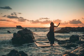 Ragazza in riva al mare danza allegramente al tramonto vicino gli scogli