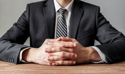 Close up of a businessman at a wooden table with crossed hands