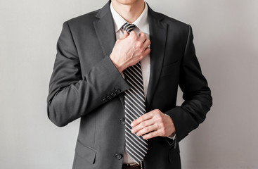 Businessman adjusting his tie,on gray background