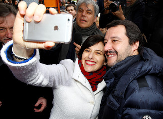 A woman takes a selfie with Northern League's leader Matteo Salvini as he arrives for a meeting with supporters in Milan