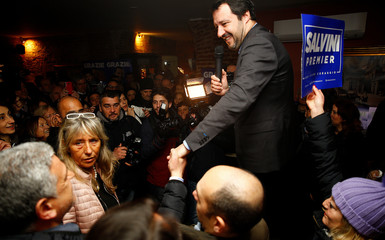 Northern League's leader Matteo Salvini shakes hands during a meeting with supporters in Milan