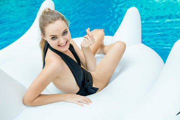 Sexy Girl in black swimming suit lying on the inflatable mattress in the swimming pool finger making a little heart shape . woman smile in bikini on white swan pool float