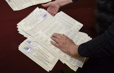 A member of a local election commission sorts ballots before starting to count votes during the presidential election in Vladivostok