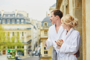Couple in white bathrobes drinking coffee together on balcony