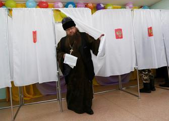 Orthodox priest Ryzhov visits a polling station during the presidential election near Krasnoyarsk