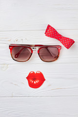 Red bow-tie, sunglasses and lips. Image of woman from sunglasses, fake lips and bow-tie. Woman fashion look with red accessories, light background.