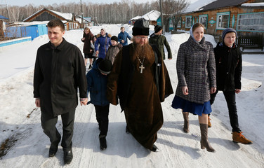 Orthodox priest Ryzhov and his family members walk to a polling station during the presidential election near Krasnoyarsk