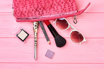 Cosmetics bag and fashion beauty accessories. Composition with makeup bag, cosmetics and sunglasses on colorful background. Women stylish essentials.