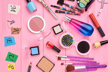 Overhead beauty essentials of modern girl. Female colorful cosmetics and tools, pink background. Paper letters make up.