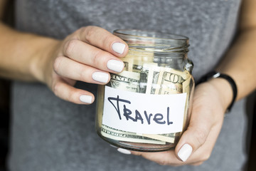 A woman is holding a piggy bank for travel full of dollars. Accumulation of finance concept