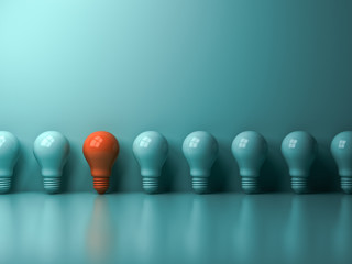 Think different concept , One orange light bulb standing out from the green incandescent lightbulbs with reflection and shadow , leadership and different creative idea concept. 3D rendering.