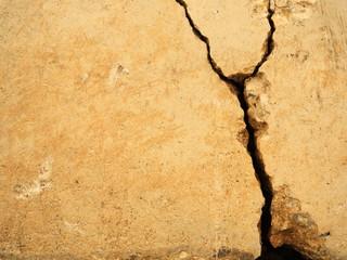 Big crack in old orange concrete wall.