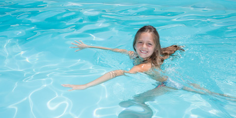 young girl learning to swim in swimming pool of city