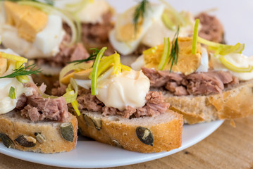 Bruschetta, snack sandwiches with tuna, egg and mayonnaise decorated by dill.
