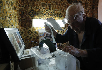 An elderly man casts his vote into a mobile ballot box during the presidential election in Moscow