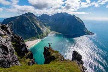 Adventurous woman looking down at Kvalvika Beach in Lofoten, Norway