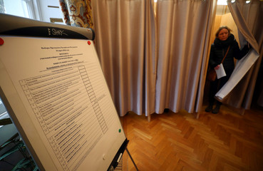 A woman walks out of a voting booth during the presidential election, at the Russian Embassy in London