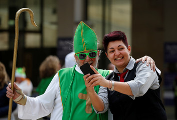 A woman takes a selfie with a participant in the St Patrick's Weekend Parade in Valletta