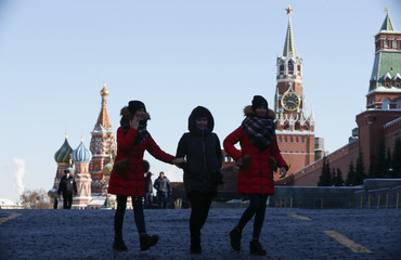 Youths walk along Red Square, with St. Basil's cathedral seen in the background, in central Moscow