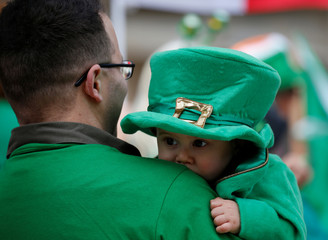 A participant carries a baby while attending the St Patrick's Weekend Parade in Valletta