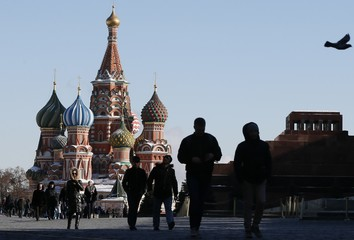 People walk along Red Square, with the Mausoleum of Soviet state founder Lenin and St. Basil's cathedral seen in the background, in central Moscow