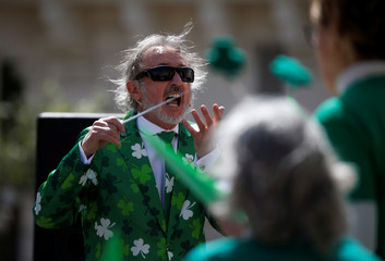 A participant conducts a choir singing Irish folk songs during the St Patrick's Weekend Parade in Valletta