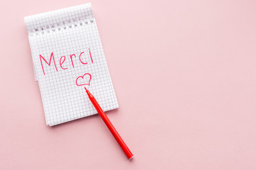 Word Merci in a notebook on a pink background