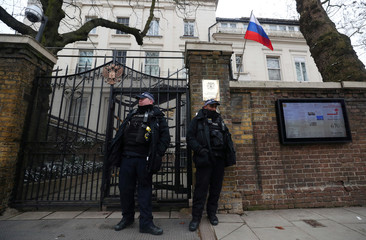 Police officers stand outside the gates of the consular section of the Russian Embassy, where voters were able to cast their votes in the presidential election, in London