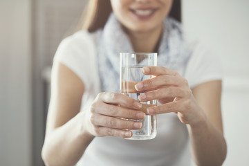 Young woman holding  pure glass of water