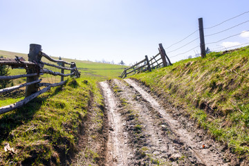 fence along the country road through hillside. lovely rural scenery