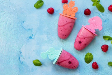 Refreshing children's ice cream popsicles (rasberry sorbet) on blue concrete background. Copy space, top view flat lay background.