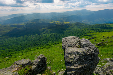 giant boulder on a cliff over the grassy hillside. beautiful summer landscape in Carpathian mountains on a cloudy day